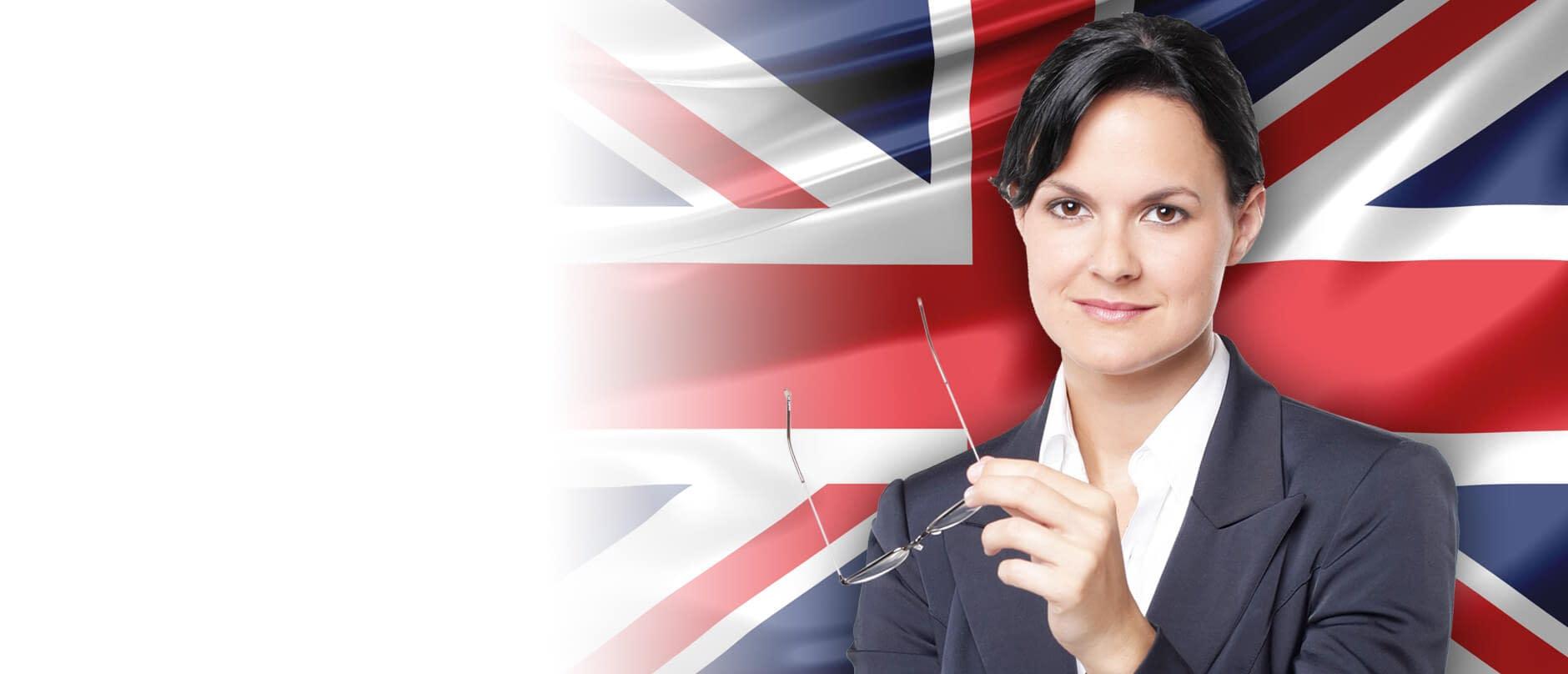 Młoda w żakiecie kobieta uśmiecha się na tle flagi brytyjskiej