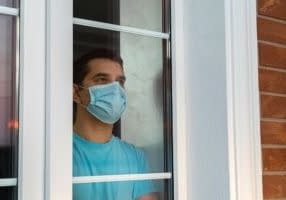 Young man in medical mask is looking out window. Coronavirus pandemic. Home quarantine, self-isolation because of the Coronavirus disease, COVID-19. Man in medical mask stay at home. Self isolation.