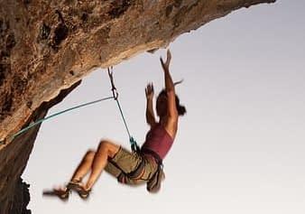 Wspinająca się kobieta odpada ze skały